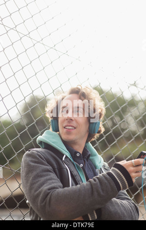 Man listening to headphones against chain link fence