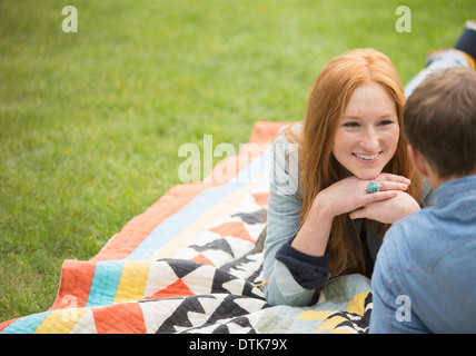 Couple relaxing on blanket in park - Stock Photo