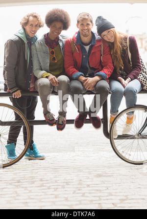 Friends smiling together on urban bike rack - Stock Photo