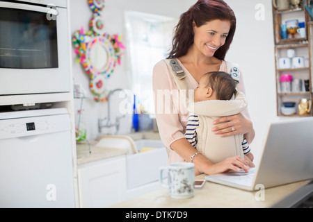 Mother holding baby boy and using laptop in domestic kitchen - Stock Photo