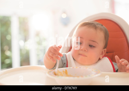 Baby boy eating in high chair - Stock Photo