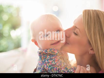 Mother kissing baby girl's cheek - Stock Photo