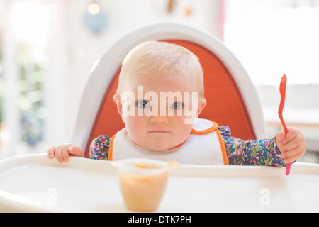 Baby girl eating in high chair - Stock Photo