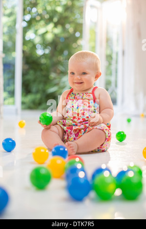 Baby girl playing with toys on floor - Stock Photo