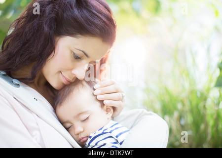 Mother holding sleeping baby girl - Stock Photo