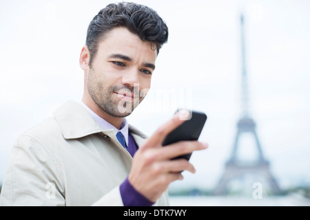 Businessman using cell phone by Eiffel Tower, Paris, France - Stock Photo