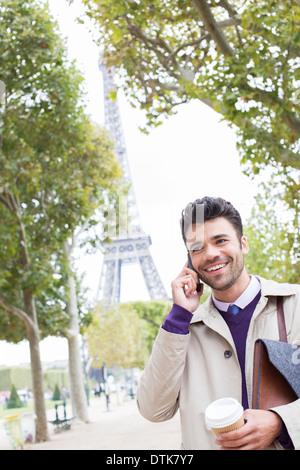 Businessman talking on cell phone near Eiffel Tower, Paris, France - Stock Photo