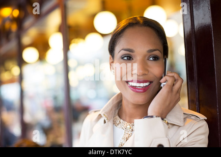 Businesswoman talking on cell phone at sidewalk cafe - Stock Photo