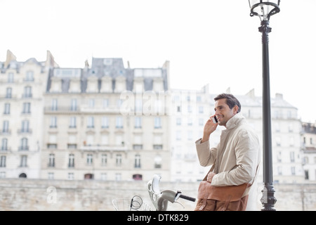 Businessman on bicycle talking on cell phone in Paris, France - Stock Photo