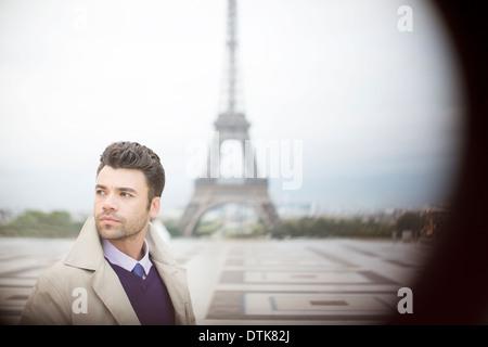 Businessman standing near Eiffel Tower, Paris, France - Stock Photo