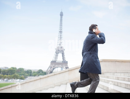 Businessman talking on cell phone and ascending steps near Eiffel Tower, Paris, France - Stock Photo