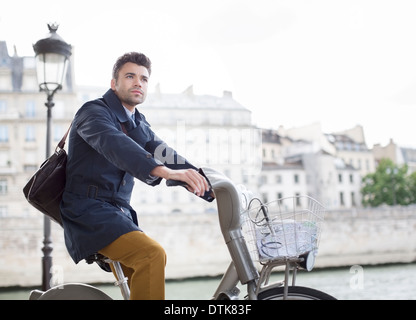 Businessman riding bicycle along Seine River, Paris, France - Stock Photo