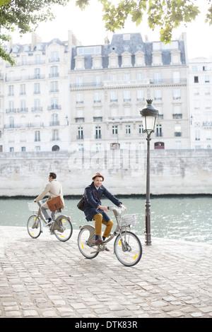 Men riding bicycles along Seine River, Paris, France - Stock Photo