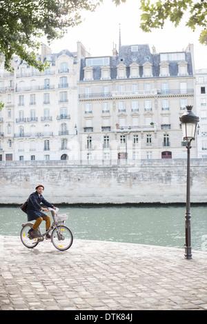 Man riding bicycle along Seine River, Paris, France - Stock Photo