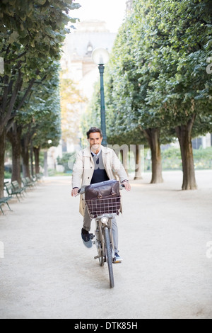 Businessman riding bicycle in park, Paris, France - Stock Photo