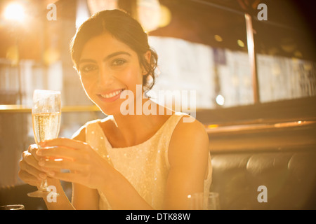 Woman having champagne in restaurant - Stock Photo