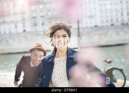 Couple laughing and running along Seine River, Paris, France - Stock Photo