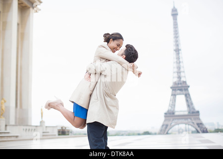 Couple hugging near Eiffel Tower, Paris, France - Stock Photo