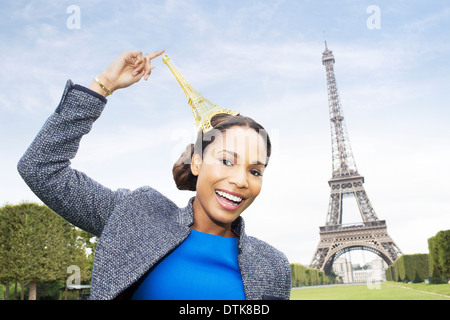 Woman posing with souvenir in front of Eiffel Tower, Paris, France - Stock Photo