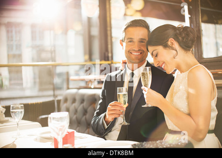 Well-dressed couple drinking champagne in restaurant - Stock Photo