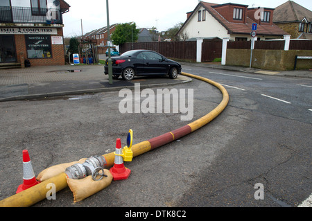 Flooded residential area and park in Staines. Water being pumped with yellow hosepipe. - Stock Photo