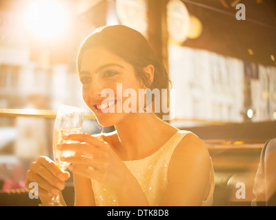 Well-dressed woman drinking champagne in restaurant - Stock Photo