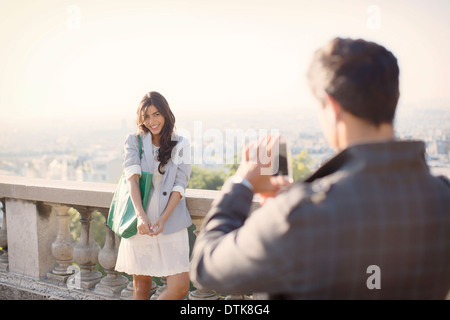 Man photographing girlfriend with Paris in background - Stock Photo