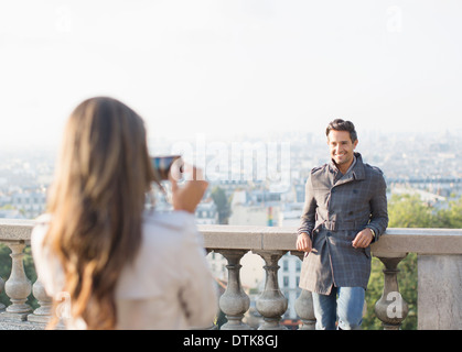 Woman photographing boyfriend with Paris in background - Stock Photo