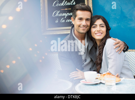 Couple hugging at sidewalk cafe in Paris, France - Stock Photo