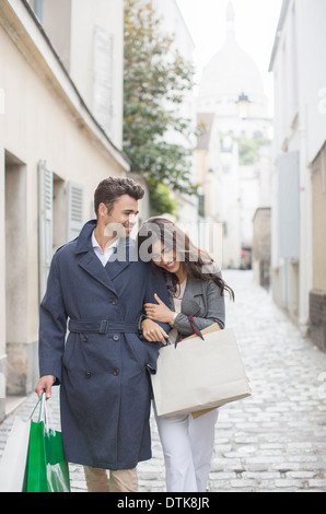 Couple carrying shopping bags on cobblestone street near Sacre Coeur Basilica, Paris, France - Stock Photo