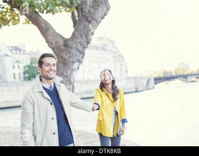 Couple holding hands along Seine River, Paris, France - Stock Photo