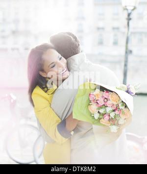 Couple with bouquet of flowers hugging along Seine River, Paris, France - Stock Photo