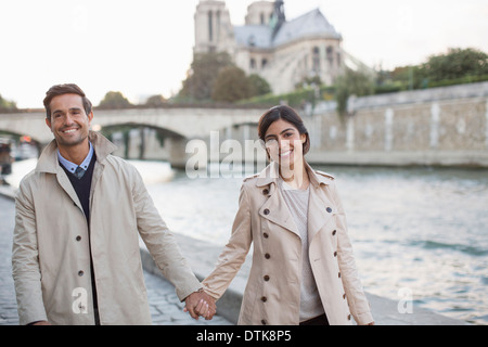 Couple holding hands along Seine River near Notre Dame Cathedral, Paris, France - Stock Photo