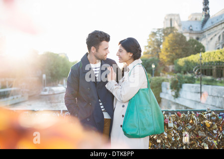 Couple standing on Pont des Arts bridge over Seine River, Paris, France - Stock Photo