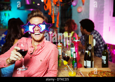 Man wearing oversized sunglasses at party - Stock Photo
