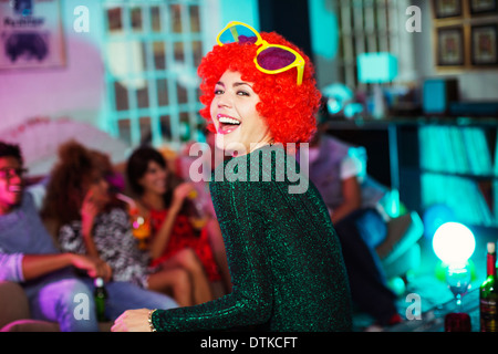Woman wearing wig and oversized sunglasses - Stock Photo
