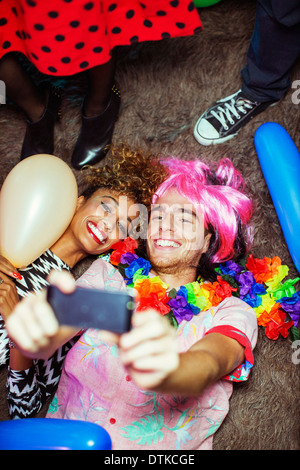 Couple taking self-portraits with camera phone on floor at party - Stock Photo