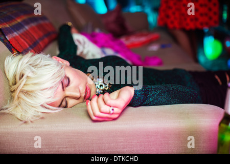 Woman sleeping on sofa at party - Stock Photo