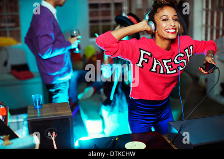 Woman playing music and dancing at party - Stock Photo