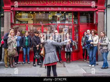 A tour group outside The Algerian Coffee Stores in Compton street London UK - Stock Photo