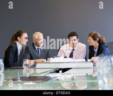 Business people looking at architectural model in office - Stock Photo
