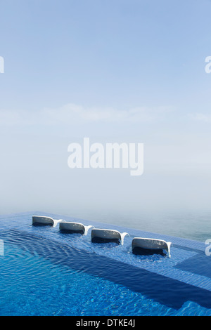 Lawn chairs in infinity pool overlooking ocean - Stock Photo