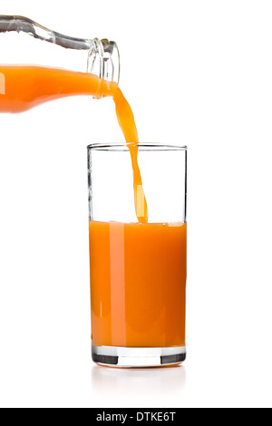 the carrot juice pouring into glass - Stock Photo