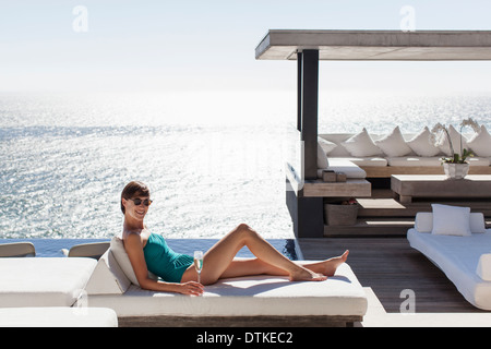 Woman relaxing on sofa outdoors - Stock Photo