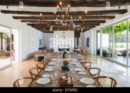 Chandelier over dining table in luxury house - Stock Photo
