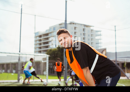 Soccer player smiling on field - Stock Photo