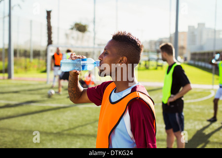 Soccer player drinking water on field - Stock Photo