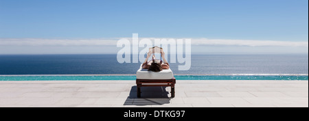 Woman relaxing on lounge chair at poolside overlooking ocean - Stock Photo