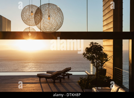 Patio of modern house overlooking ocean at sunset - Stock Photo