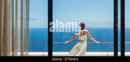 Woman looking at ocean from balcony - Stock Photo